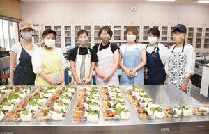 企業などから提供された材料を使って出来上がった宅配弁当とプロジェクトの賛同者=唐津市の呼子公民館