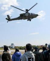 飛行展示されたヘリコプターにカメラを向ける見物客ら=吉野ヶ里町の目達原駐屯地