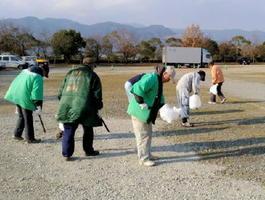 手分けして会場内のごみを拾い集める出店者たち=吉野ケ里歴史公園