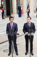共同記者発表する安倍首相(左)とフランスのマクロン大統領=23日、パリの大統領府(共同)