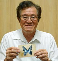 ミカドアゲハの標本写真を手にする吉田英範さん=佐賀市天神の佐賀新聞社