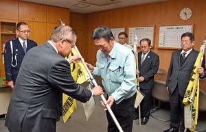 牟田正明会長(左)から交通安全旗を受け取る事業者の代表者=神埼市の神埼署