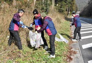 28日開催の東西松浦駅伝を前に、コース沿道のごみ拾いをする大川町体協チームのメンバー=唐津市相知町