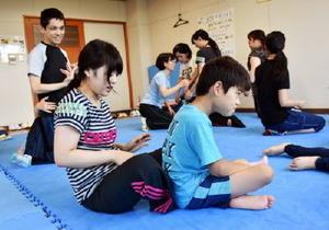 トレーナーの学生の支援を受け、体幹を保つ訓練に励む小学4年のアヤト君=8月19日、波戸岬少年自然の家