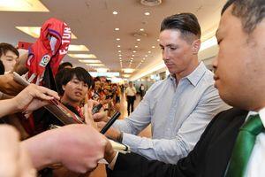 詰めかけたファンにサインで応じるフェルナンド・トーレス選手=15日午前11時すぎ、東京都の羽田空港