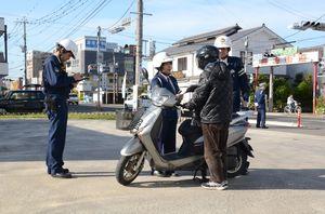 交通違反をしたミニバイクを呼び止め、注意するとともに切符を切る佐賀南署の署員=佐賀市