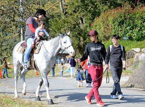 サテライト会場の「クラブリオ」で乗馬を楽しむ親子=江北町山口