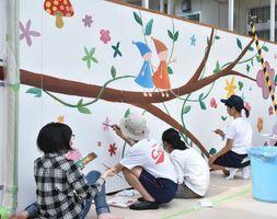 渡り廊下の壁に絵を描く東原庠舎中央校の美術部員たち=多久市の新型コロナウイルスワクチン接種センター