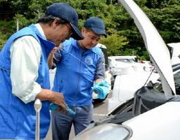 ドライバーの休憩中に、エンジンルームの無料点検を実施する青年部ら=佐賀市大和町の道の駅