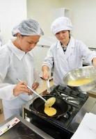 短大生(右)の指導を受けながら、どら焼きの生地を焼く留学生=佐賀市の西九州大短期大学部