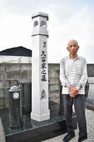 「若き日、赴任先の島から見た灯台を模したお墓」の前でほほ笑む久冨さん=佐賀市巨勢町