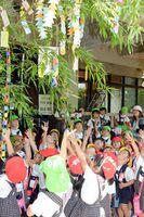 七夕飾りを見上げながら手を上げる園児ら=佐賀市の金立山いこいの広場