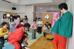 豆に見立てた紙を鬼役の職員に投げつける子どもたち=吉野ヶ里町の三田川児童館