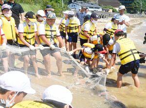 網にかかった魚が見えて引く手に力を込める児童たち=唐津市の幸多里の浜