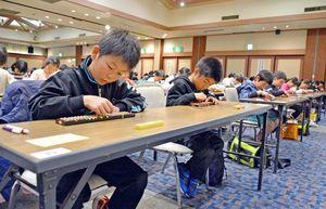 そろばんをはじきながら計算する参加者=佐賀市大和町のホテル龍登園