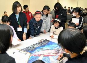 池田学さんの作品「Bait」の拡大パネルをのぞき込み、モチーフを探す子どもたち=佐賀市の県立美術館