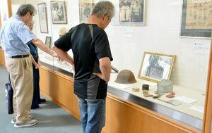 日用品や戦地で使われていた品々を集めたコーナー=佐賀市の市立図書館