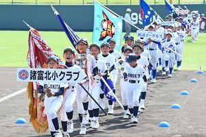 全日本学童軟式野球佐賀県大会の開会式で、前年優勝の諸富北小クラブを先頭に力強く行進する選手たち。参加129チームが全国大会を目指して熱戦を繰り広げる=佐賀市のみどりの森県営球場