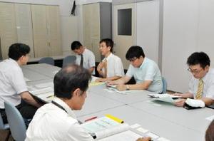 県法務私学課の担当者(左)に私学助成の拡充を求める佐賀私教連のメンバーら=県自治会館別館