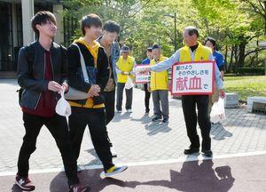 ボードを首から提げ、献血への協力を呼び掛ける県内のライオンズクラブメンバー=佐賀市の佐賀大学