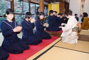 慣れない手つきながら作法に倣って茶を飲む塩田中3年の生徒=嬉野市塩田町の本應寺