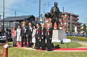 北海道知事(右から4人目)や札幌市長も参加して開かれた島義勇像(右奥)の除幕式=佐賀市城内の佐賀城公園「西御門橋」南側