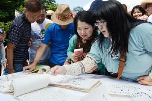 34年前の作文を懐かしそうに読む参加者たち=有田町の先人陶工の碑前