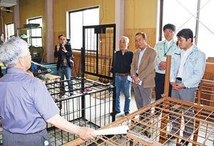 イノシシ用の箱わなの説明を受ける参加者=みやき町の野生獣類捕獲技術研修センター