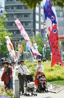 20日、東京・六本木の東京ミッドタウンでアーティストらがデザインした「アートこいのぼり」のイベントが始まった。初夏を思わせる陽気の中、薄着の親子連れらがカラフルなこいのぼりが風に揺れる様子を楽しんでいた