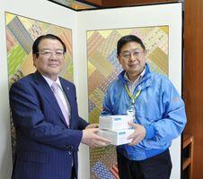 樋口久俊市長(左)にマスクを手渡す光武博之社長=鹿島市役所