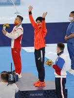 男子個人総合で金メダルを獲得し、表彰式で手を振る橋本大輝(中央)=有明体操競技場