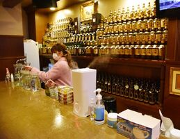 感染対策に気を配りながら開店準備をする小山千恵さん。通常午後8時からの営業で、21日以降は「休まざるを得ない」という=18日、佐賀市白山のスナック「ベリーベリー」