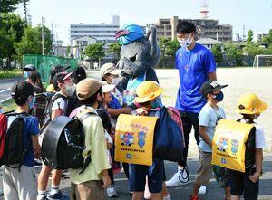 登校してきた児童と笑顔で会話する德川慎之介選手(右奥)=佐賀市の勧興小