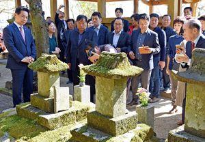 王仁博士の石碑についての説明を聞く田東平郡守(左)ら訪問団のメンバー=神埼市神埼町