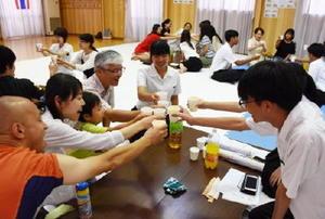 受け入れ家族と乾杯をするタイの留学生たち=佐賀市高木町の古賀空手道場
