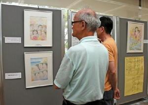 沖縄の子どもたちを描いた作品を見る来場者たち=佐賀市のアバンセ