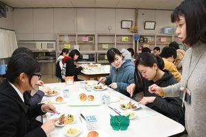 アドバイスを受けながら、フォークとナイフの使い方を学ぶ生徒=佐賀市の佐賀商業高