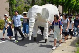 島袋さん(左から3番目)の制作した白象オブジェとともに街歩きに出発する参加者=佐賀市本庄町の佐賀大キャンパス