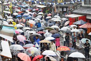 小雨の中、開幕した有田陶器市。来場者の傘の波が行き交う皿山通り=4月29日、有田町