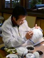 「力強く濃い線」を心掛け、筆先に集中する藤本秀一郎さん。「目が肥えた人が多く、気が抜けない」作業が続く=有田町の柿右衛門窯