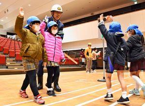 交通指導員の誘導を受けて、横断歩道の正しい渡り方を学んだ園児たち=神埼市中央公民館