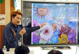 エクアドルで描く壁画の案を見せるミヤザキケンスケさん=佐賀市の県国際交流プラザ