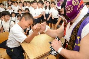 将火怒選手と腕相撲で力を競う児童=三日月小
