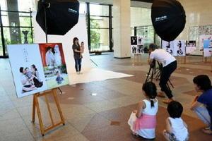 特設スタジオで撮影する親子=佐賀市の県庁県民ホール