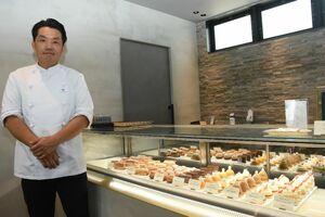 Patisserie ANNのオーナーシェフ安洪珉さんとケーキ、タルトなどの洋菓子=唐津市鏡