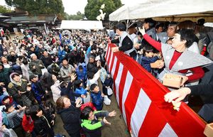 雨が降る中、福豆に手を伸ばす大勢の人たち=佐賀市の佐嘉神社