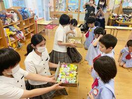 松ぼっくりで作ったアマビエを園児に配る虹ノ松原研究班の生徒たち=唐津市の虹の森こども園