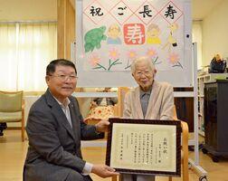 伊東健吾町長(左)から祝い状を受け取る吉野ヶ里町内最高齢の中島多美子さん=神埼市の「愛夢かんざき」