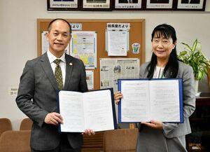 協定書に調印した大野博之副理事長(左)と深川千幹校長=佐賀市の川副中