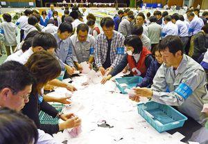 開票が始まり、作業にあたる職員ら=10月22日、佐賀市の市村記念体育館